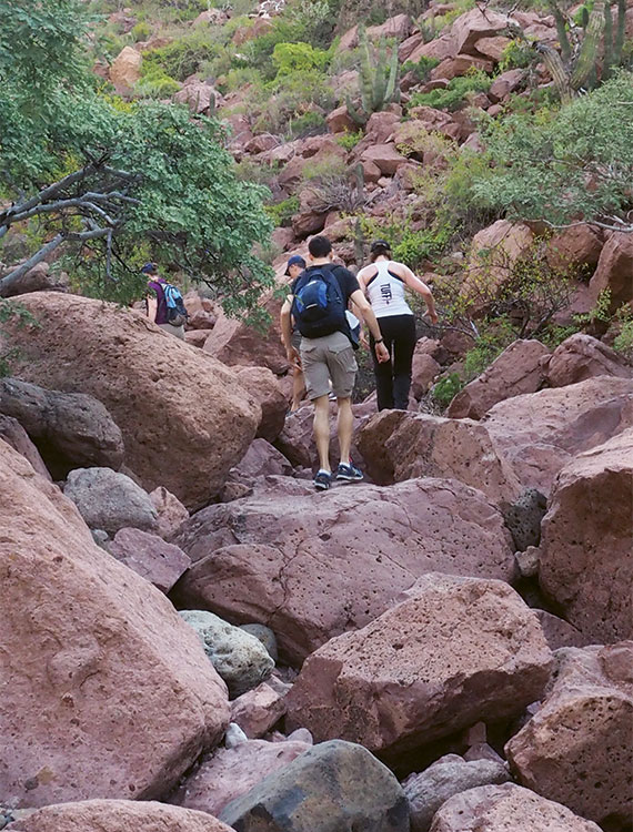 Passengers on a five-mile, 600-foot climb over rocks and boulders to a coastal lookout point atop Isla Partida.
