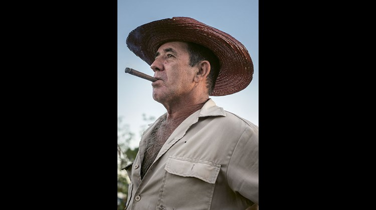 A farmer enjoys a cigar at the prize-winning organic farm and restaurant El Paraiso in the hills of Vinales.