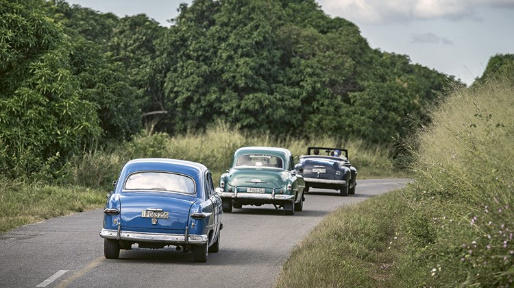 Classic cars make their way through western Cuba toward Vinales after turning off the Carretera Central, Cuba's main east-west highway.
