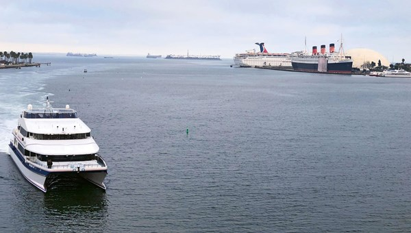 The Catalina Express underway with the Queen Mary and a Carnival Cruise Line ship in the background.