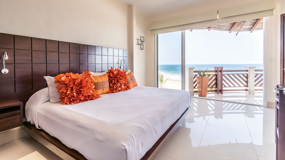 A bedroom with a balcony and sweeping ocean views.