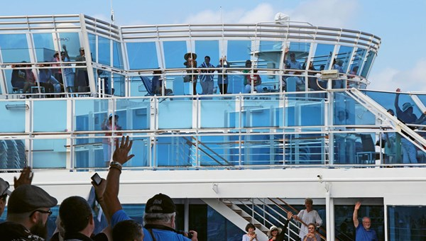 Passengers onboard the Island Princess and visitors at the Miraflores Locks exchange waves as the cruise ship transits the Panama Canal.