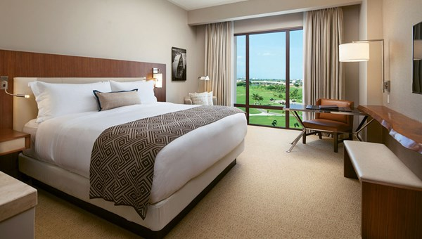 A deluxe king room at the Santa Maria hotel and golf resort with a view of the golf course and a mola patterned blanket on the bed.