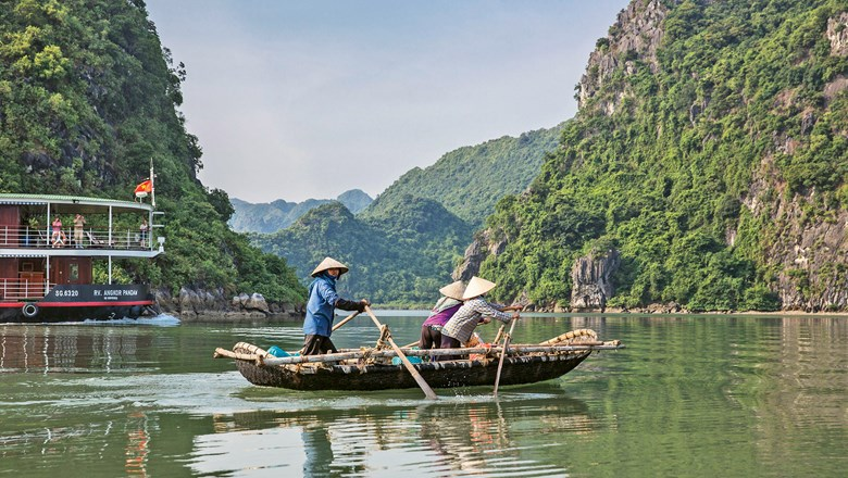 The Angkor Pandaw cruises past a rustic boat and impressive karst formations in Ha Long Bay, Vietnam.