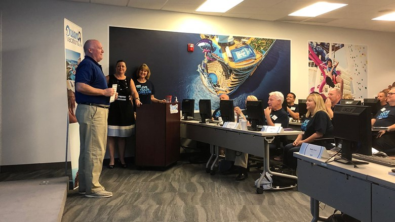 A new CruiseOne/Cruises Inc/DreamVacations franchisee is recognized for training achievement in a room decorated with murals of Royal Caribbean International ships.