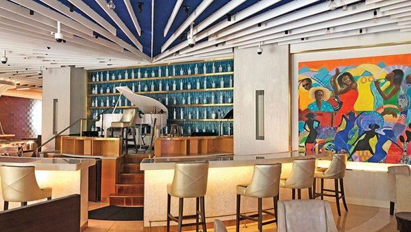 The Grand Hyatt Baha Mar's West lobby is anchored by a small bar area, colorful art pieces and an elevated grand piano.