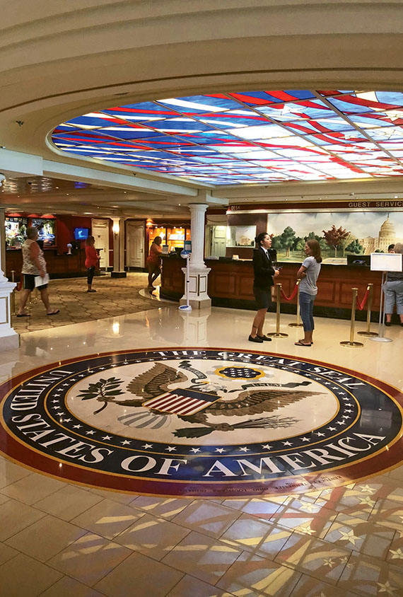 An image of the Great Seal of the United States adorns the floor of the guest services lobby on Norwegian's Pride of America.