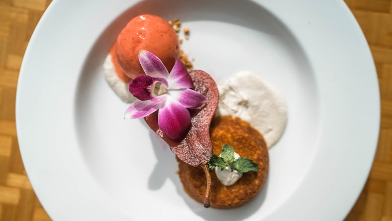 The Reef Bar and Market Grill now serves a vegan hibiscus-poached pear with almond cake and sweet cream, topped with a scoop of strawberry sorbet.