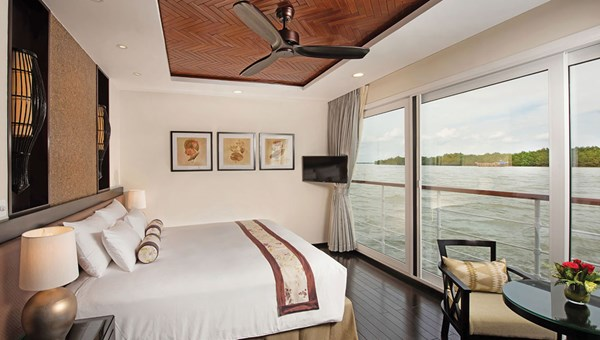 A suite onboard the ship with floor-to-ceiling, sliding glass doors.