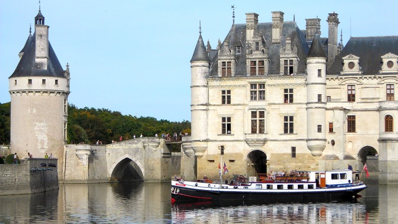 European Waterways' Nymphea hotel barge crusing by Chateau de Chenonceau which spans the River Cher in France.