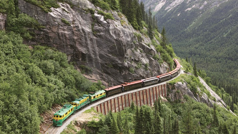 A White Pass & Yukon Route Railway diesel-electric locomotive hugs the mountainside.