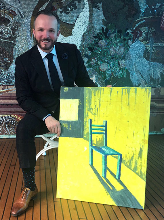 Uniworld senior vice president of global sales Kristian Anderson and the painting of a chair given to him at the company's Kickoff event.