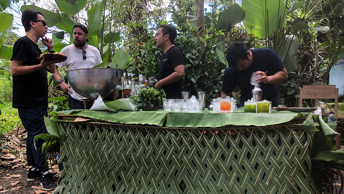 A makeshift bar in a jungle clearing served drinks with Balinese ingredients to guests on a Silversea Cruises shore excursion. The skirt on the bar is made from palm fronds stripped from trees, but the tip of the frond is not stripped so the leaves will continue to support the tree.