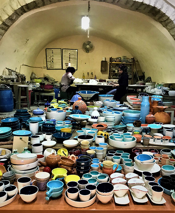 Ceramics for sale at Iraq al-Amir Women's Association. The women in the back are creating ceramic leaves, to be glazed and painted.