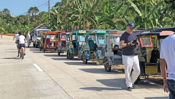 "A caravan of ""tricycles"" along a road in Romblon."