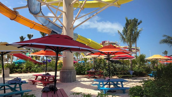Umbrella-shaded picnic tables in the Thrill Waterpark.