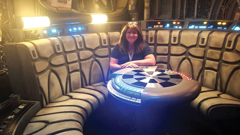 Mouse Fan Travel CEO Beci Mahnken sitting at the iconic Dejarik game table on the queue of Millennium Falcon: Smugglers Run.
