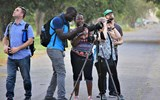 Guyana naturalist Leon Moore helps a visitor line up her phone camera to his telescope to photograph a crimson crested woodpecker at Georgetown's Botanical Gardens.