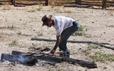 Ranch owner Tommy Kenyon checks branding irons sitting in hot embers.