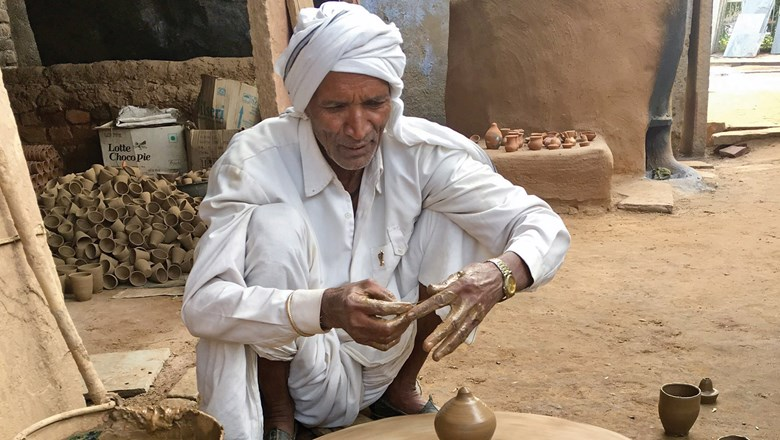 An elderly potter and his wheel in Abhaneri village.