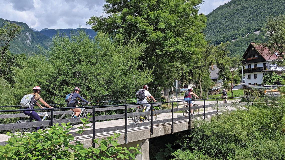 Cyclists crossing a small bridge.