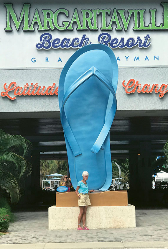 The author poses before the giant, peacock blue sandal sculpture at the entrance to the resort.