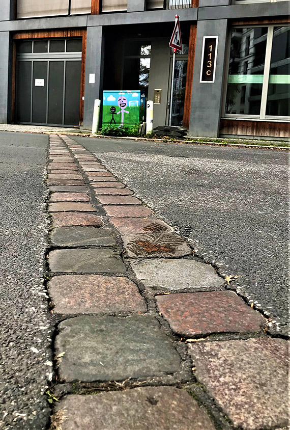 A line of cobblestones in a street indicate where the Berlin Wall stood, with the West German neighborhood Kreuzberg to the left and the East Berlin neighborhood Friedrichshain to the right.