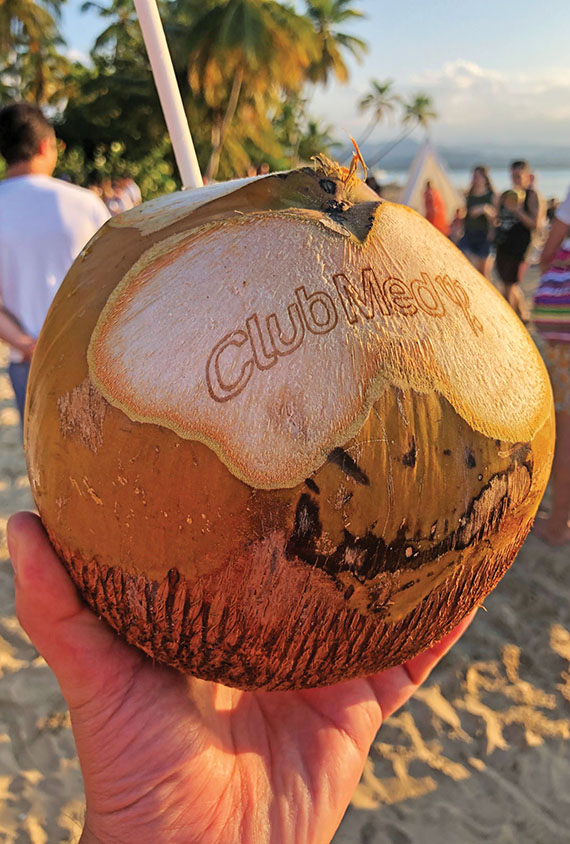 "A coconut with a paper straw served during the ""sunset ritual"" at the resort, Club Med's first ""Eco-Chic"" property."