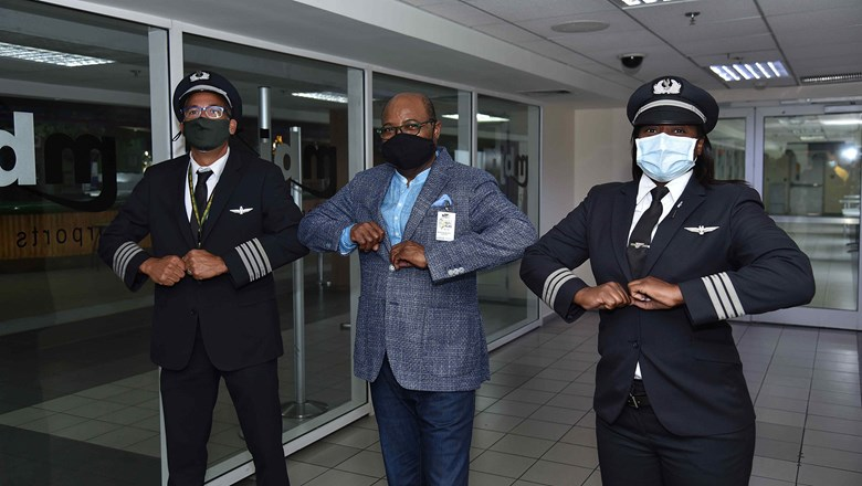 In June, Edmund Bartlett, Jamaica's minister of tourism, center, bumped elbows with American Capt. Shaun Nelson and first officer Bethoya Powell, who flew the first commercial flight into Sangster airport after a 3-momth hiatus.