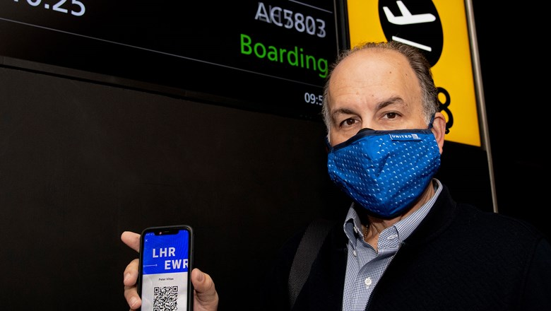 Internova's Peter Vlitas holds up his unique QR code on the CommonPass health pass before boarding his flight from London to Newark.