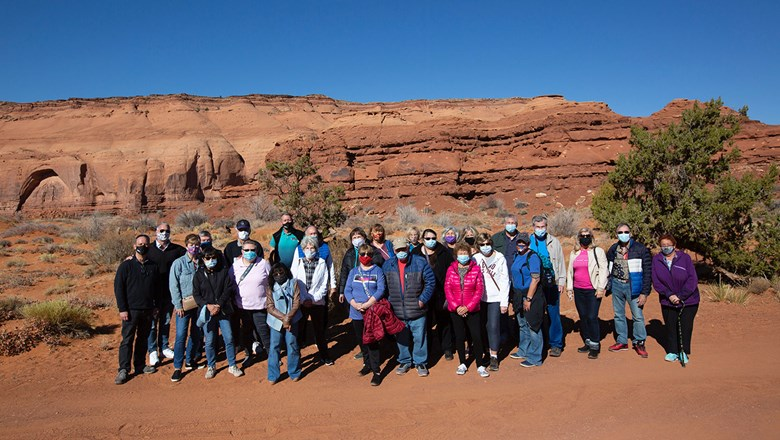 Guests wearing masks for a group photo on a Globus tour in Monument Valley, Ariz.