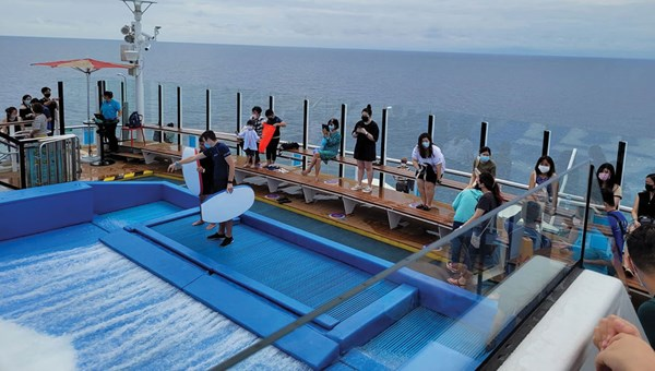 The new normal: Passengers keep their distance at the ever-popular Flowrider surf simulator.