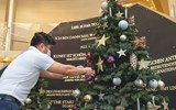A passenger puts an ornament on a Christmas tree on Hapag-Lloyd's Europa 2, which has been sailing from both Germany and in the Canary Islands.