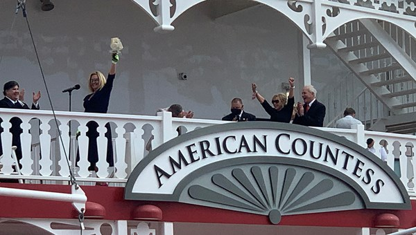 American Queen CEO John Waggoner, far right, claps as his daughter, Angie Hack, prepares to christen the American Countess.
