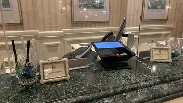 The check-in counters at the Grand Floridian resort at Walt Disney World have plexiglass shields and cups for sanitized and used pens.