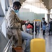 Traveler on phone at airport wearing mask [Credit: DimaBerlin/Shutterstock.com]