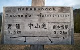 A rustic sign on the Nakasendo in English and Japanese points walkers toward Tsumago and Nagiso.
