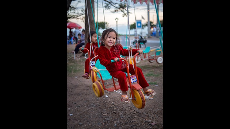 All along the Mekong, the cities and towns in Cambodia and Vietnam recall an ugly past but focus on a promising future. During a sailing aboard Uniworld's River Orchid, Mark Edward Harris caught a glimpse of that future first hand. Pictured here, a child enjoying a ride at a neighborhood amusement park in Kampong Cham, Cambodia.