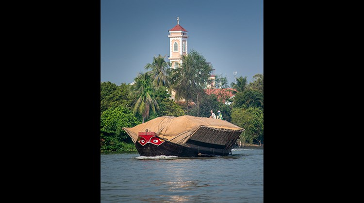 Grain is transported up river in Vietnam past Cai Be's Catholic Cathedral.