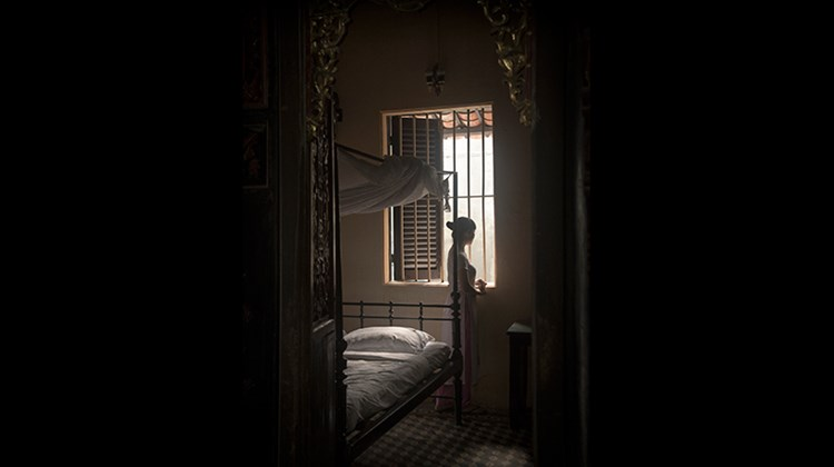 A docent in a bedroom at the Huynh Thuy Le House, a late19th-century structure in Sa Dec, made famous by its connection to best-selling French novelist Marguerite Duras.