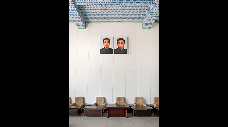 Portraits of Kim Il Sung and Kim Jong Il hang in the waiting room at the Tumangang train station.