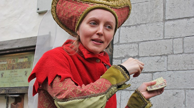 A staffer at Olde Hansa restaurant, in period costume, urging passersby to try the eatery. Olde Hansa, housed in a medieval building, features period menus as well as costumed personnel.