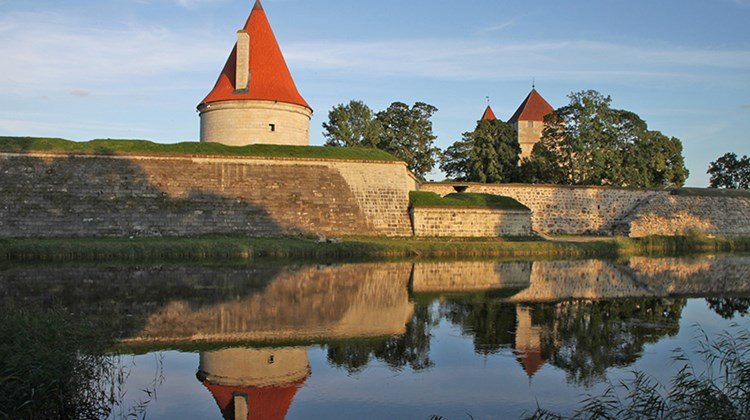 Another view of Saaremaa's Episcopal Castle, at right, and an associated tower, both reflected in the castle's moat.
