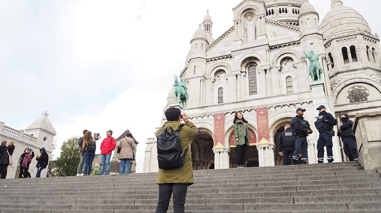 At Sacre Coeur, visitors posed for pictures while police stood nearby.