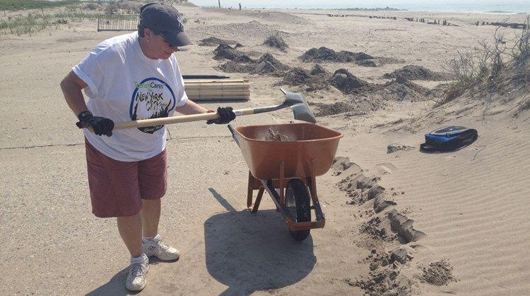 Jackie Amari, of American Express, shovels sand to clear a path near the beach at Fort Tilden.