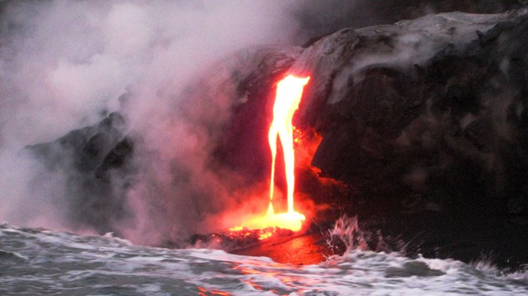 Reaching up to 2,500 degrees Fahrenheit, molten lava oozes onto a growing black sand beach.