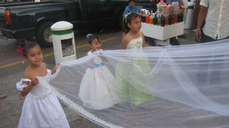 Young girls hold a bride's veil at a street wedding in Acapulco. TW photo by Gay Nagle Myers