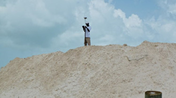 A worker tests the quality of a pile of sand on Castaway Cay.