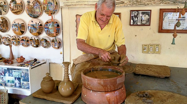 Azariel Santander Alcantera, a celebrated potter in the town of Trinidad, demonstrates his talent at his pottery wheel.