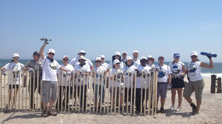 Travel Weekly Editor in Chief Arnie Weissmann and members of the snow-fencing project team stand next to a completed portion of fence at Fort Tilden.